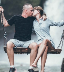 man and woman sitting on wooden swing while kissing